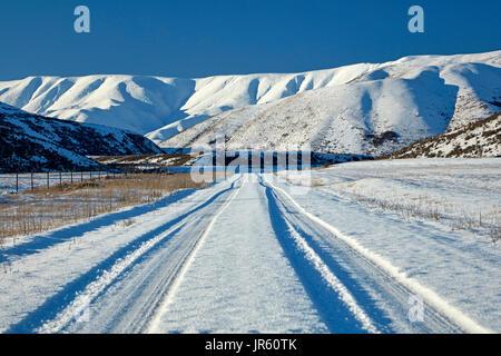 Hawkdun Range and snowy track to Falls Dam, Maniototo, Central Otago, South Island, New Zealand - Stock Photo