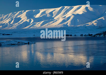 Falls Dam and Hawkdun Range in winter, Maniototo, Central Otago, South Island, New Zealand - Stock Photo
