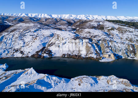 Snow around Blue Lake, St Bathans, and Hawkdun Range, Maniototo, Central Otago, South Island, New Zealand - drone - Stock Photo