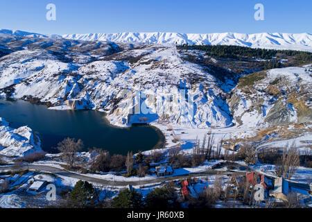 Snow around Blue Lake, St Bathans, and Hawkdun Range, Maniototo, Central Otago, South Island, New Zealand - drone - Stock Photo