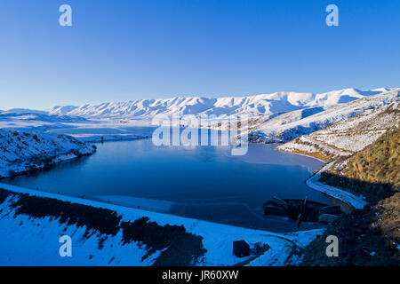 Falls Dam and Hawkdun Range in winter, Maniototo, Central Otago, South Island, New Zealand - drone aerial - Stock Photo