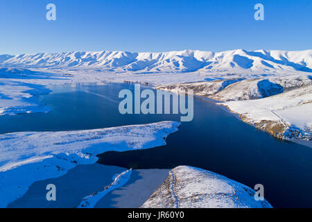 Ice at the edge of Falls Dam, and Hawkdun Range in winter, Maniototo, Central Otago, South Island, New Zealand  - Stock Photo