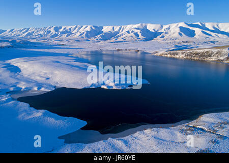 Falls Dam and Hawkdun Range in winter, Maniototo, Central Otago, South Island, New Zealand - drone aerial - Stock Photo