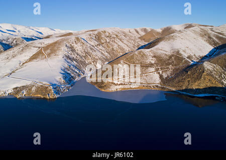 Ice at the edge of Falls Dam in winter, Maniototo, Central Otago, South Island, New Zealand - drone aerial - Stock Photo