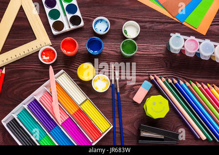 School supplies on a red background, paints and brushes - Stock Photo