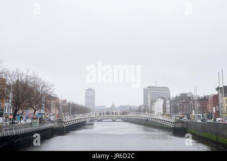 Black & White view of  beautiful irish landmark in dublin city. Famous ha'penny bridge set in a dublin cityscape - Stock Photo