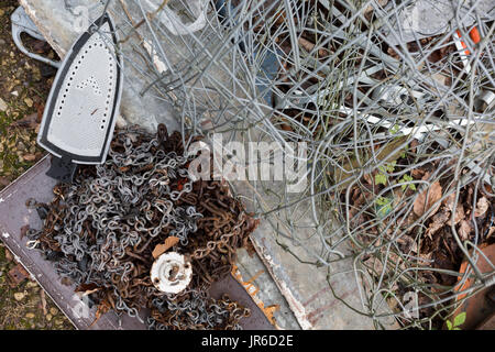 Household objects scrap metal including chain, an iron and fencing await recycling on rural land, on 30th July 2017, - Stock Photo