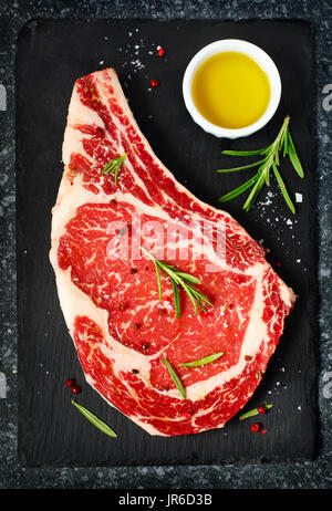 Raw Dry Aged Steak with rosemary and olive oil - Stock Photo