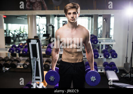 very power athletic guy , execute exercise with dumbbells, in gym - Stock Photo