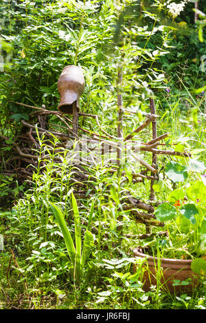 picturesque rustic landscape in russian village with broken ceramic jug on lath fence on green overgrown garden - Stock Photo