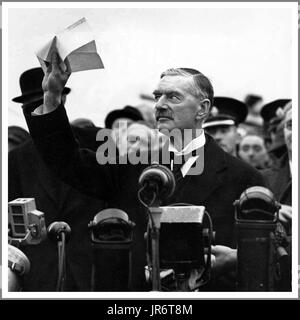 Neville Chamberlain holds 'the' piece of paper proudly aloft signed by both Hitler and himself on his return from - Stock Photo