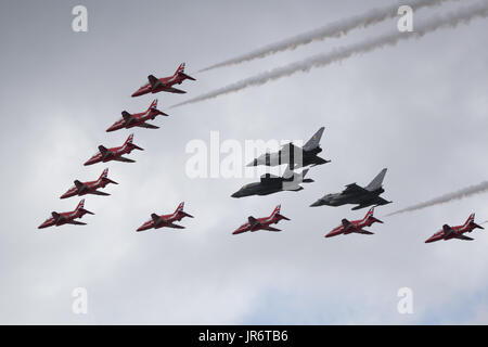 Fairford, Gloucestershire, UK - July 10th, 2016: RAF BAE Red Arrows Flypast in Formation with EuroFighter Typhoons - Stock Photo