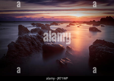 Bude, Cornwall, United Kingdom at sunset, beautiful seascape, sea against rocks with a slow shutter speed - Stock Photo