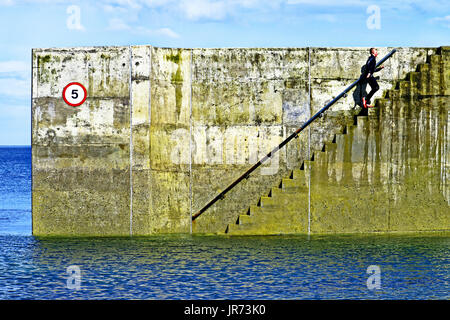 Boy in wet suit running up harbour steps Cullercoats - Stock Photo