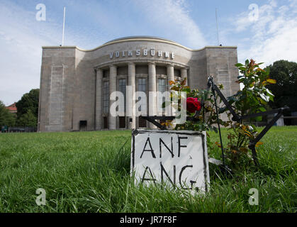 Berlin, Germany. 4th Aug, 2017. Flowers, a star and sign are reminding of the 'Raeuberrad' (lit. robber wheel) sculpture - Stock Photo