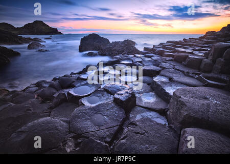 sunset over basalt rocks formation Giant's Causeway, Port Ganny Bay and Great Stookan, County Antrim, Northern Ireland, - Stock Photo