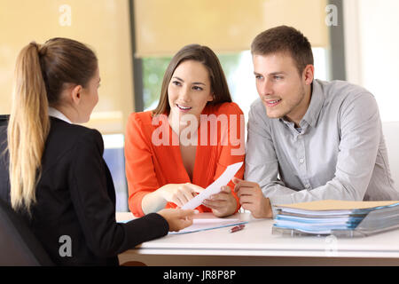 Two happy customers solving doubts about a contract with the saleswoman at office - Stock Photo