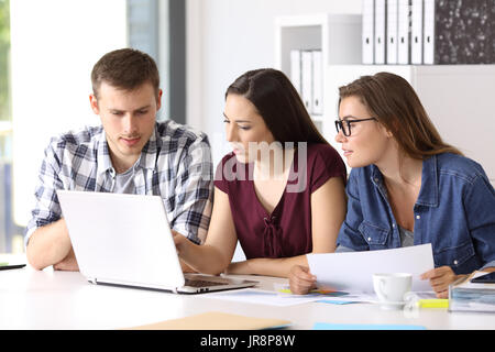 Three entrepreneurs coworking on line with a laptop sitting in a desktop at office - Stock Photo