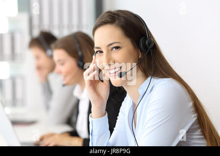 Happy telemarketer looking at you at office with other workers in the background - Stock Photo