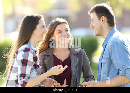 Three happy friends having a conversation and laughing in the street - Stock Photo