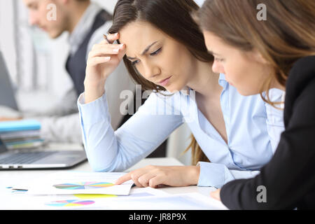 Two worried businesswomen analyzing paper growth graphs at office - Stock Photo