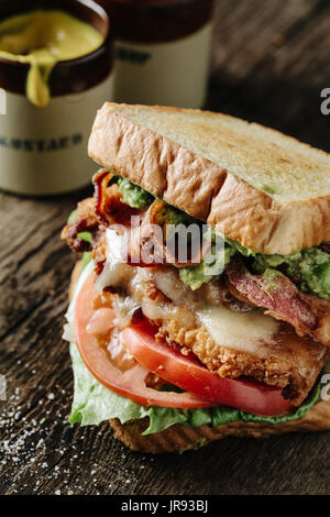 Chicken and Avocado BLT sandwich on rustic surface - Stock Photo