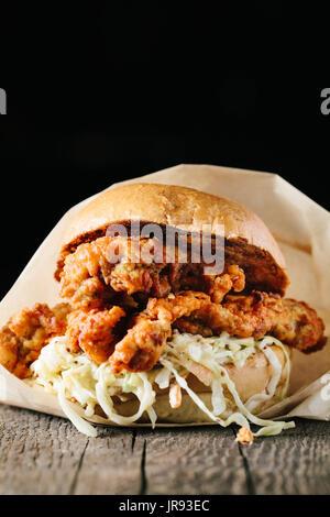 Southern style fried crispy chicken sandwich on dark background - Stock Photo