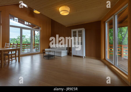 Living room in a wooden organic house. Wooden floor, wooden ceiling. Corky walls. White cupboard. Panoramic windows - Stock Photo