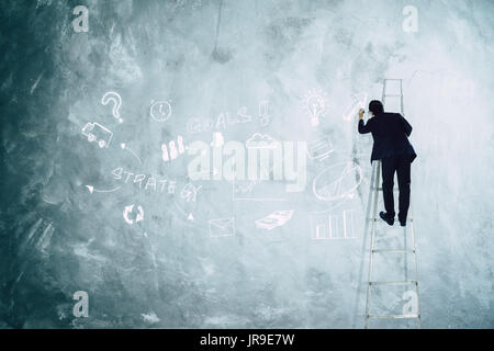 Men drawing development graph strategy on grey wall . - Stock Photo