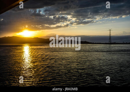 Setting sun with golden rays off the coast of Sicily in the Mediterranean Sea. - Stock Photo