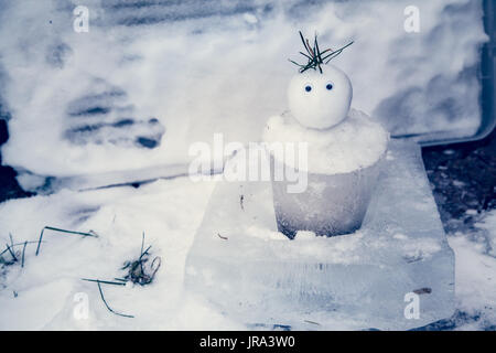 Small snowman made of ice in Winter after fresh snowfall and has an ice bucket-shaped body. - Stock Photo