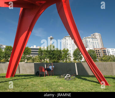 Seattle Space Needle seen from the Olympic Sculpture Park where a cyclist rests in the shade of The Eagle - Stock Photo