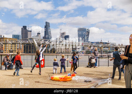 Street entertainer soliciting tips entertaining children by blowing large colourful bubbles, Bankside, Embankment, - Stock Photo