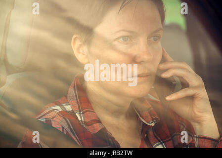 Worried woman talking on mobile phone in car, concerned adult caucasian female person during telephone conversation