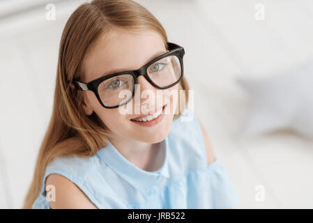 Portrait of adorable girl wearing glasses smiling - Stock Photo