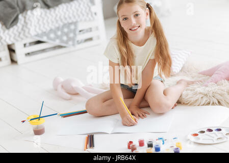 Beautiful girl looking into camera while drawing - Stock Photo