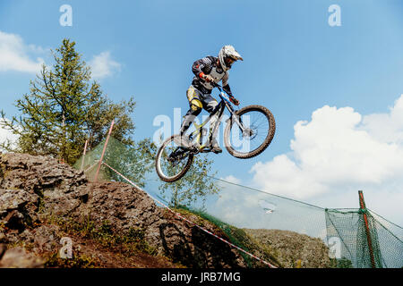 rider on bike gap jump from mountain during National championship downhill - Stock Photo