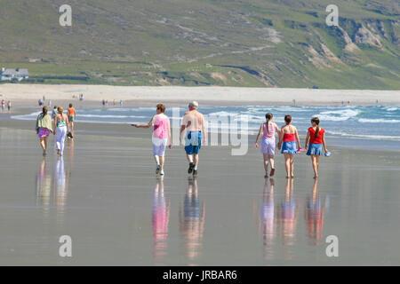 People enjoying a summer walk on Achill Island Sandy Beach, Co.Mayo, Ireland - Stock Photo