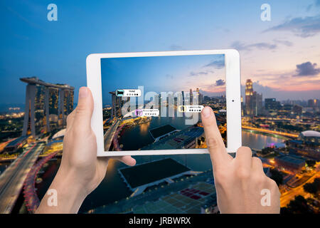 Hand holding smart phone use AR application to check relevant information about the spaces around customer. Singapore - Stock Photo