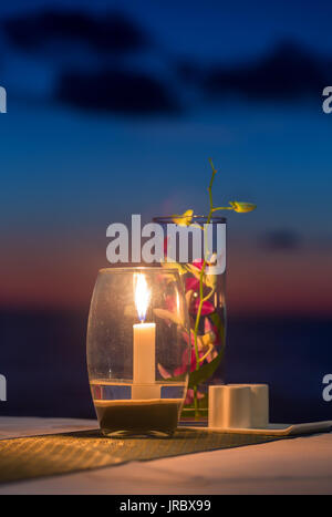 Candle on a table at sunset view restaurant on Koh Kood island, Thailand - Stock Photo