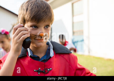 Boy with face paint using walkie talkie while looking away during birthday party in yard - Stock Photo