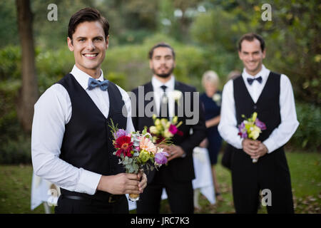 Portrait of bridegroom and best man standing with bouquet of flowers in garden - Stock Photo