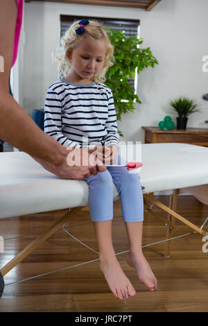 Doctor examining reflexes of patient knee in clinic - Stock Photo