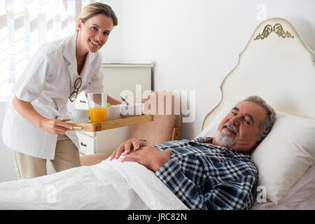 Portrait of female doctor serving food to senior patient relaxing on bed in nursing home - Stock Photo
