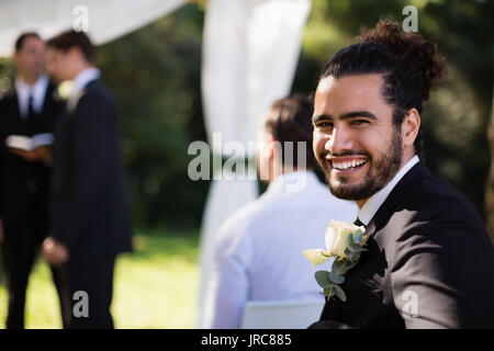 Portrait of handsome groomsman smiling in park during wedding - Stock Photo
