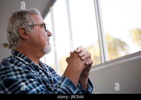 Thoughtful senior man looking away while sitting on wheelchair in retirement home - Stock Photo