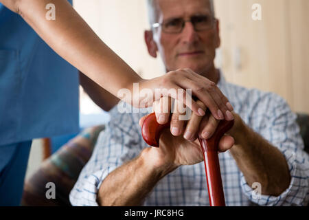 Close up of female doctor and senior man hands holding walking cane in retirement home - Stock Photo