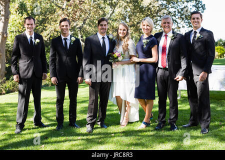 Portrait of bride and groom standing with guests in park - Stock Photo