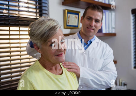 Physiotherapist stretching neck of a female patient in the clinic - Stock Photo