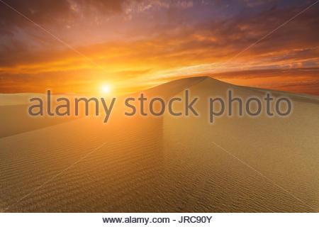 Beautiful desert landscape on the background of a fiery sunset. - Stock Photo